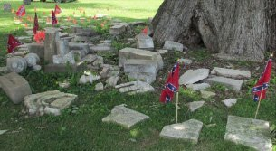 Civil War monuments broken into many pieces with a small confederate flag .